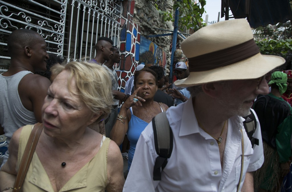 FILE - In this March 22, 2015 file photo, tourists visit Hamel Alley as a Cuban woman smokes a cigar in the background, in Havana, Cuba. Tourism numbe