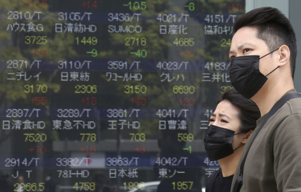People walk by an electronic stock board of a securities firm in Tokyo, Monday, April 16, 2018. Shares were mixed in Asia after an upbeat start to the