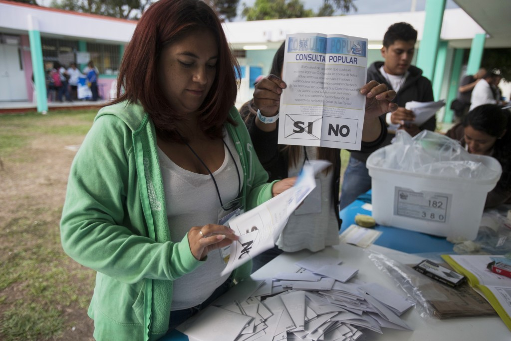 "An electoral worker shows a ballot marked ""yes,"" during a plebiscite concerning a border dispute with Belize, in Guatemala City, Sunday, April 15, 201"