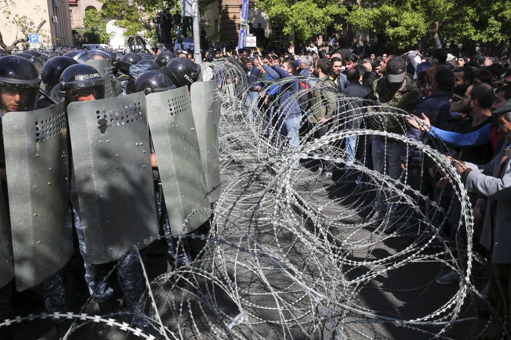 Police stop opposition demonstrators as they march to protest the former president's shift into the prime minister's seat in Yerevan, Armenia, Monday,