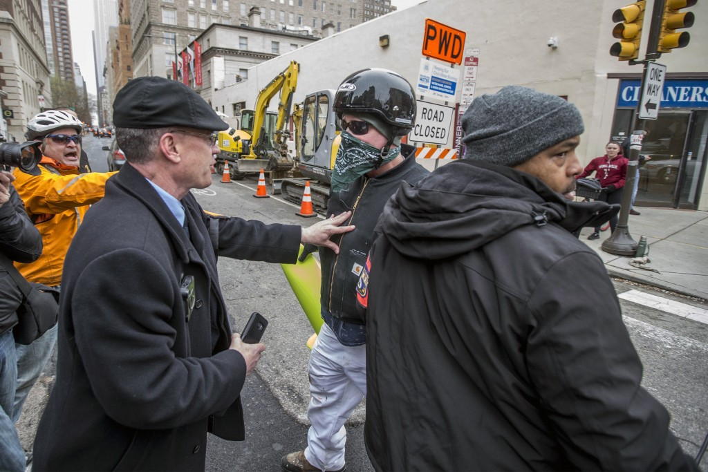 A Philadelphia plain clothes police officer, left, pushes back on a counter protester, center, who tried to disrupt a local Black Lives Matter demonst