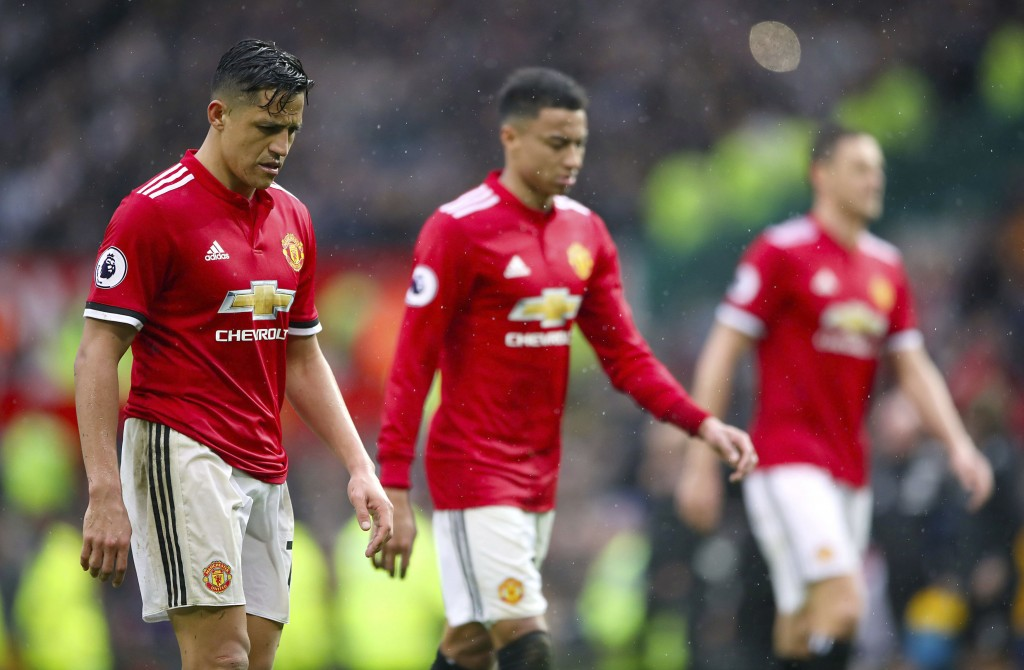 Manchester United's Alexis Sanchez, left, leaves the pitch dejected after the final whistle during the English Premier League soccer match against Wes