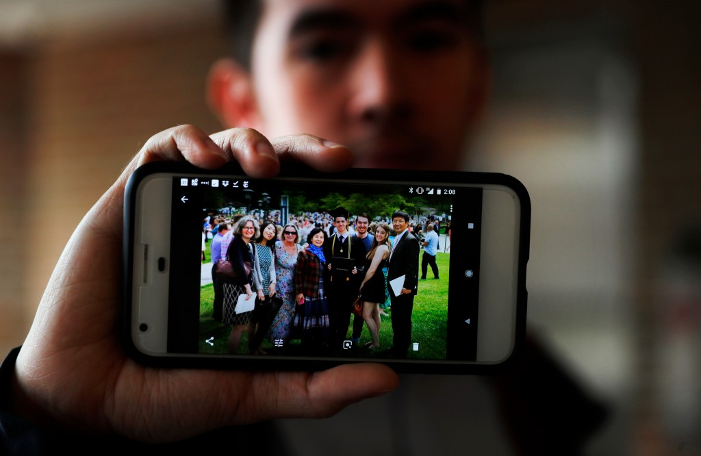 In this Tuesday, April 10, 2018, photo, Amos Cao, son of Chinese Rev. John Sanqiang Cao, holds a family photo showing his father, far right, in Ann Ar