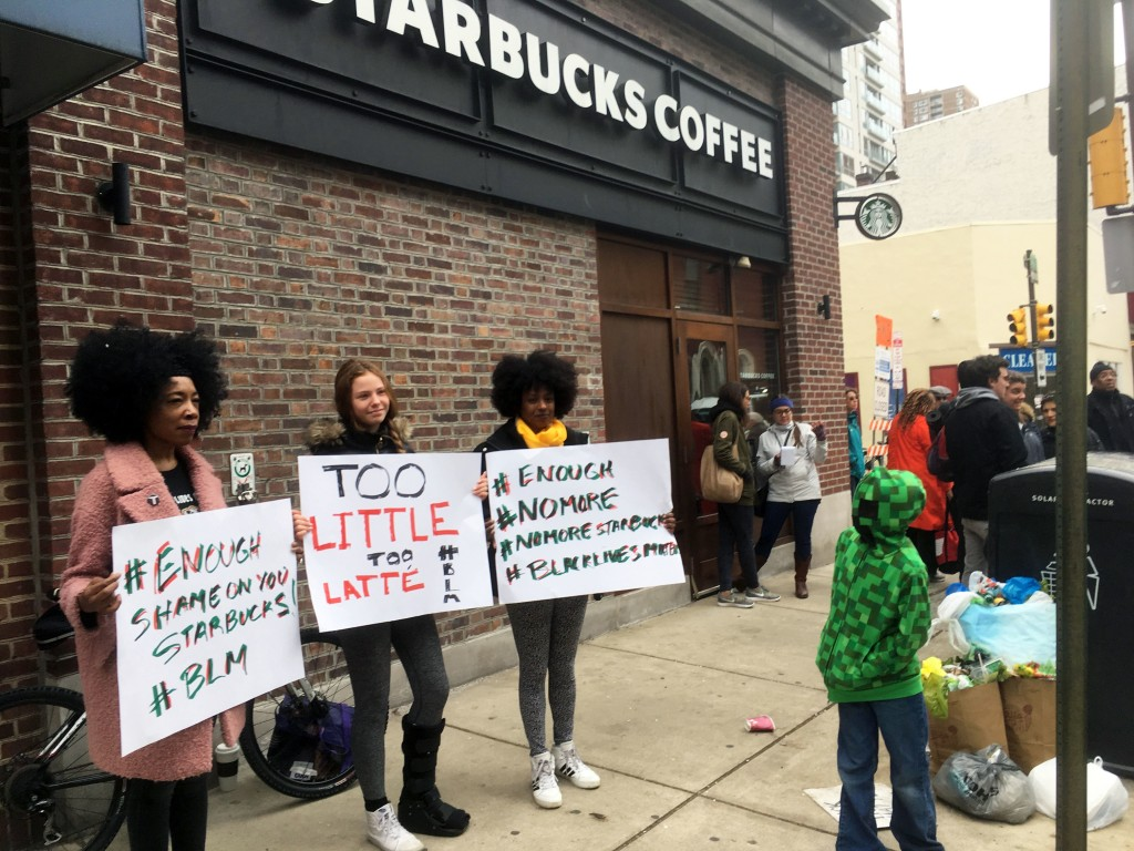 Protesters gather outside a Starbucks in Philadelphia, Sunday, April 15, 2018, where two black men were arrested Thursday after Starbucks employees ca