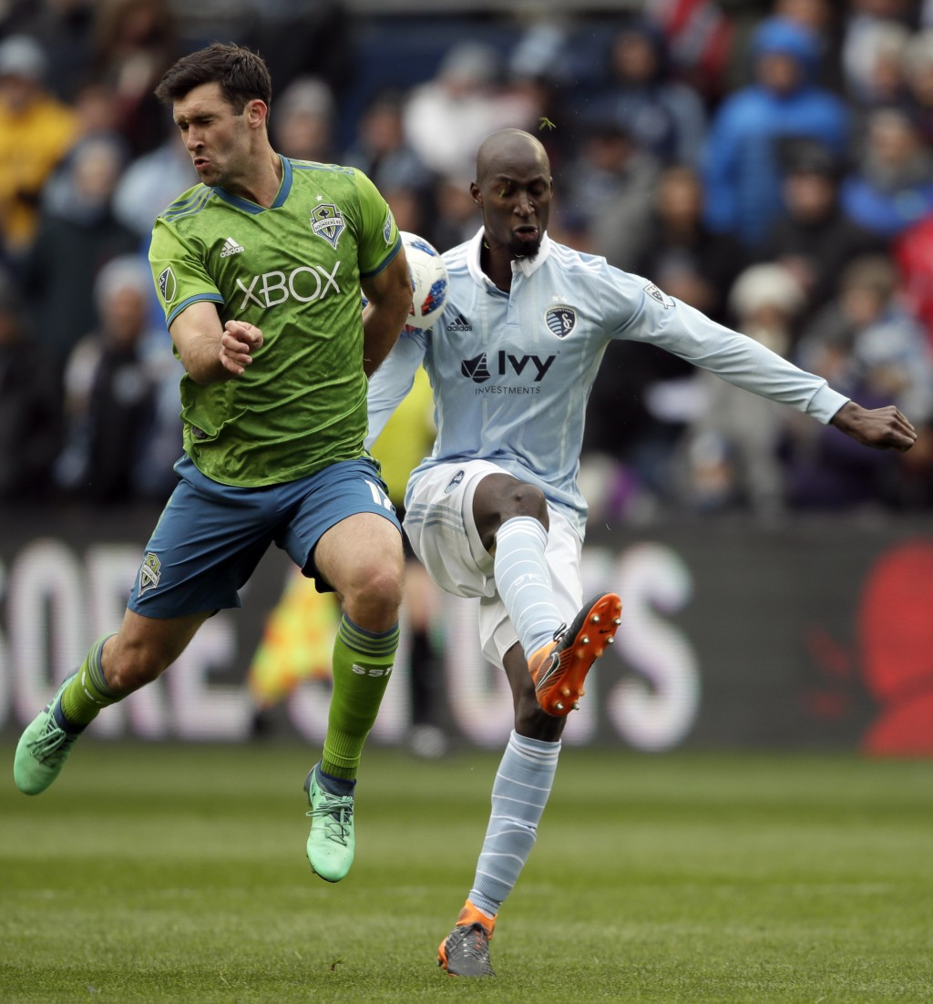 Seattle Sounders defender Will Bruin, left, blocks a kick by Sporting Kansas City defender Ike Opara, right, during the first half of an MLS soccer ma