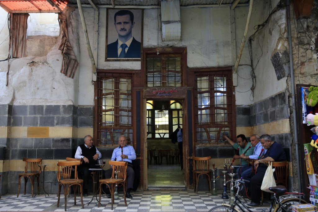 Syrians smoke water pipes at a coffee shop at the Hamidiyeh market, in the Old City of Damascus, Syria, Sunday, April 15, 2018. Syria's President Bash