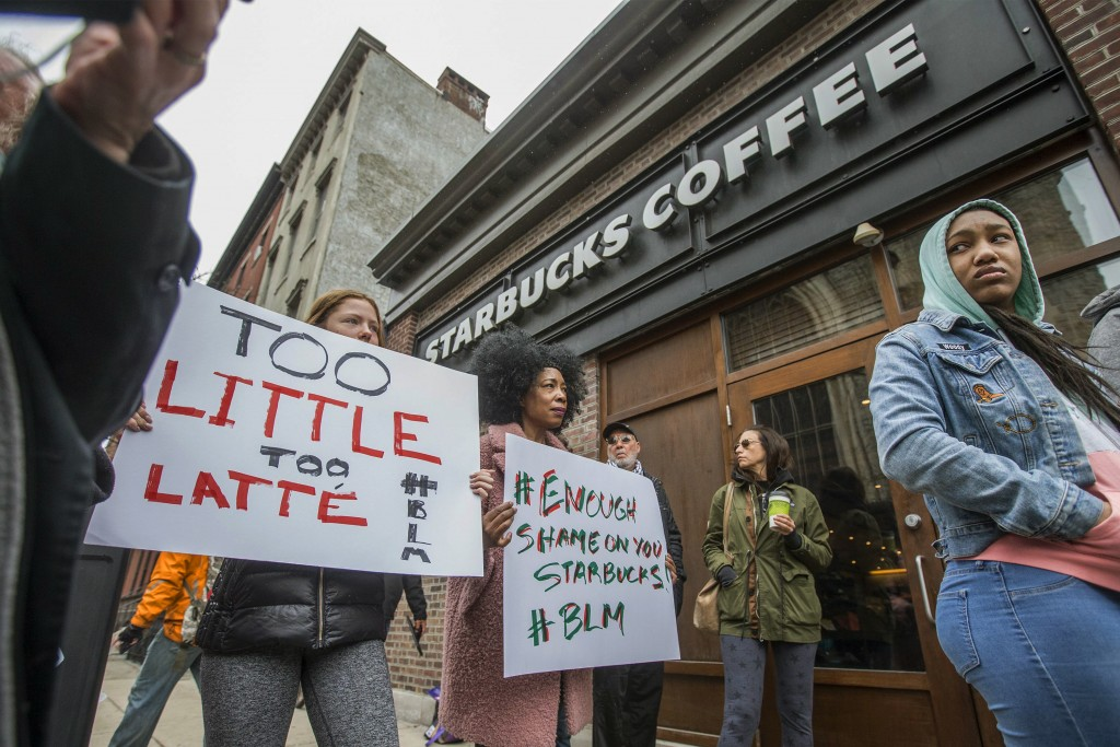 Protesters gather outside of a  Starbucks in Philadelphia, Sunday, April 15, 2018, where two black men were arrested Thursday after employees called p