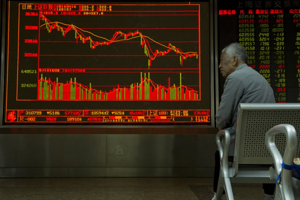 An investor monitors stock prices at a brokerage in Beijing Monday, April 16, 2018. Shares were mixed in Asia after an upbeat start to the week, with