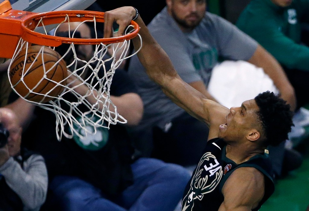 Milwaukee Bucks' Giannis Antetokounmpo dunks during overtime in Game 1 of an NBA basketball first-round playoff series against the Boston Celtics, in