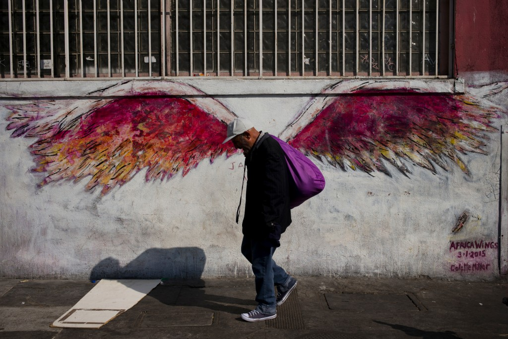 """FILE - In this Friday, Sept. 1, 2017, file photo, a man walks past a mural of angel wings titled """"Africa Wings"""" by artist Colette Miller in Los Angele"""