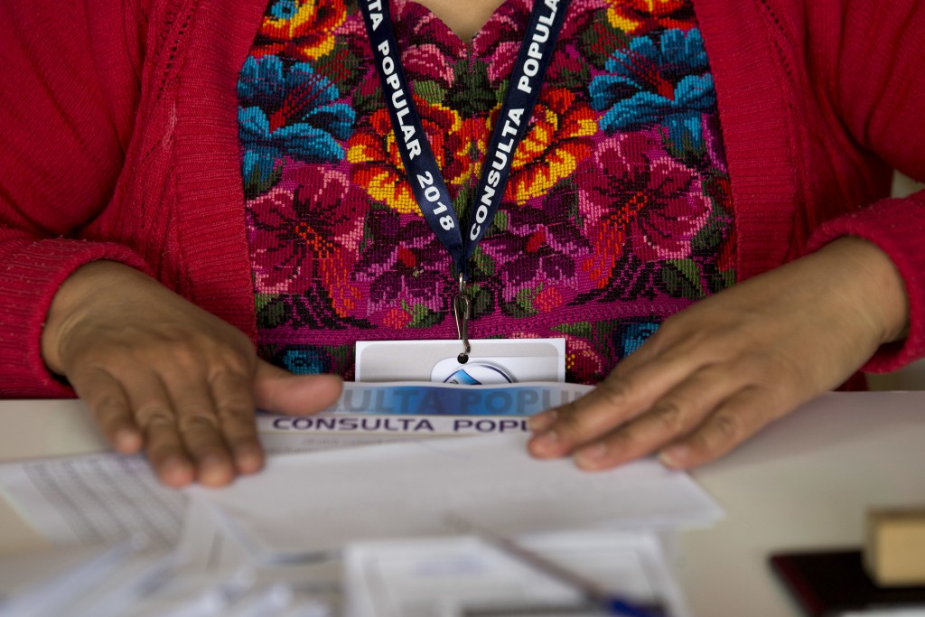 An electoral volunteer folds a ballot during a plebiscite concerning a border dispute with Belize, in San Pedro Sacatepequez, Guatemala, Sunday, April