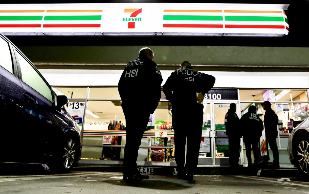 FILE - In this Jan. 10, 2018, file photo, U.S. Immigration and Customs Enforcement agents serve an employment audit notice at a 7-Eleven convenience s