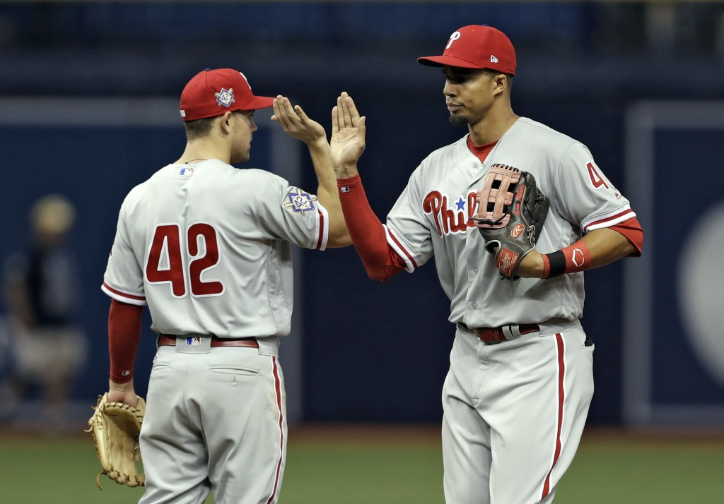 Philadelphia Phillies right fielder Aaron Altherr, right, high-fives second baseman Scott Kingery after they defeated the Tampa Bay Rays in a baseball