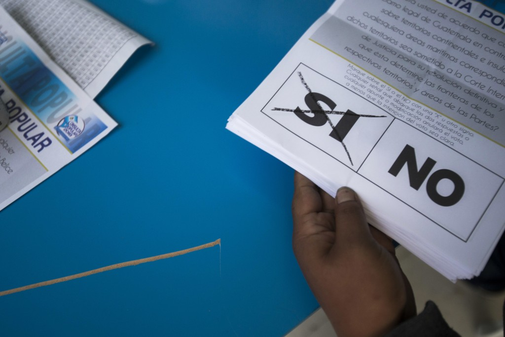 "An electoral worker holds ballots marked ""yes,"" during a plebiscite concerning a border dispute with Belize, in Guatemala City, Sunday, April 15, 2018"