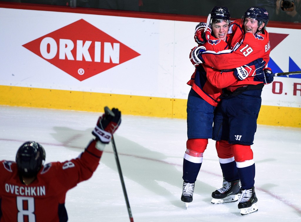Washington Capitals right wing T.J. Oshie, center, celebrates his goal with Nicklas Backstrom (19), of Sweden, and left wing Alex Ovechkin (8), of Rus