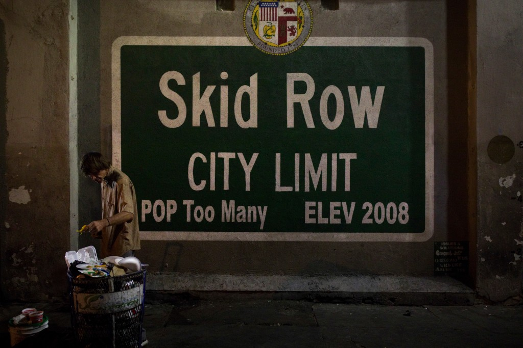 FILE - In this Oct. 28, 2017, file photo, a homeless man takes food from a trash can in Los Angeles' Skid Row area, home to the nation's largest conce