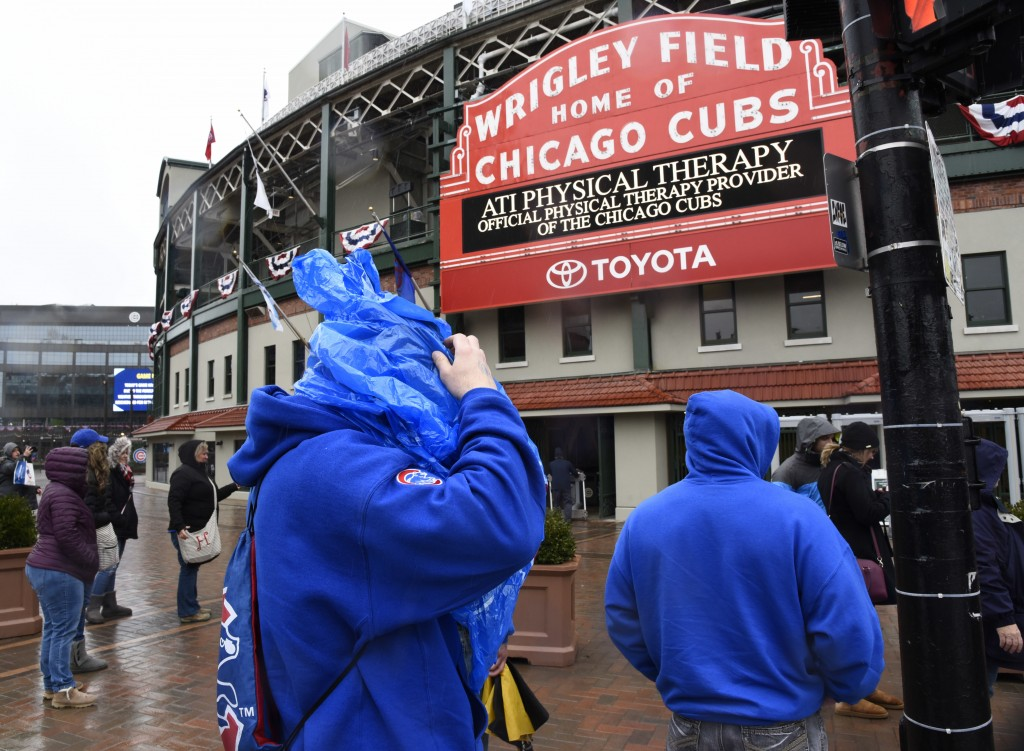 Fans do their best to stay warm and dry outside Wrigley Field after a baseball game between the Atlanta Braves and the Chicago Cubs was postponed on S