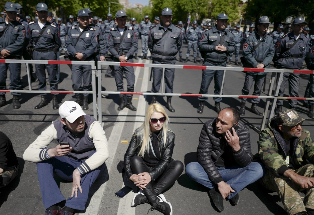 Opposition demonstrators sit in front of police line to protest the former president's shift into the prime minister's seat in Yerevan, Armenia, Monda