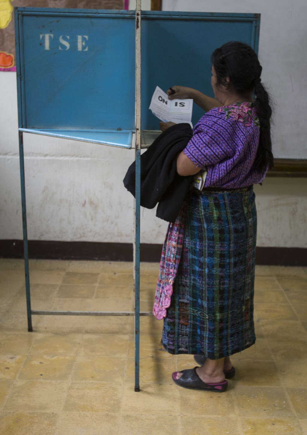 A woman holds her ballot during a plebiscite concerning a border dispute with Belize, in Guatemala City, Sunday, April 15, 2018. Guatemalans are decid