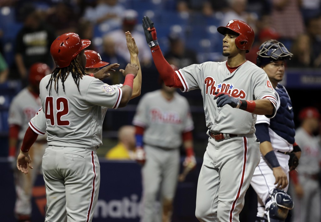 Philadelphia Phillies' Aaron Altherr, second from right, high-fives Scott Kingery (partially obscured) and Maikel Franco, right, after his three-run h