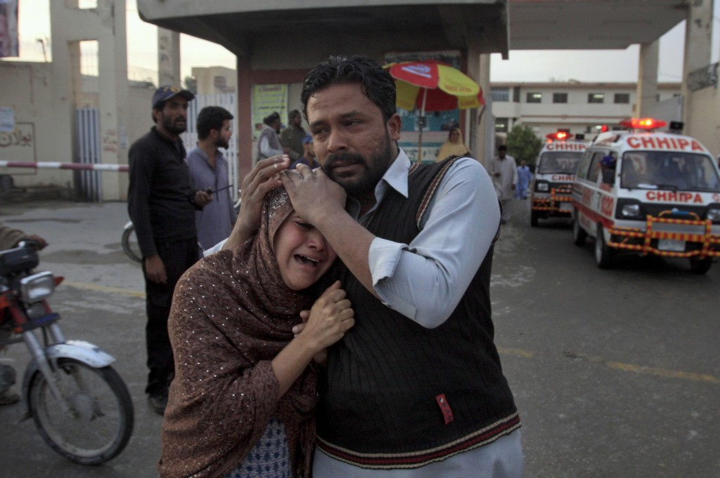 A man comforts a Christian woman who lost her husband in a deadly shooting incident, outside a hospital in Quetta, Pakistan, Sunday, April 15, 2018. P