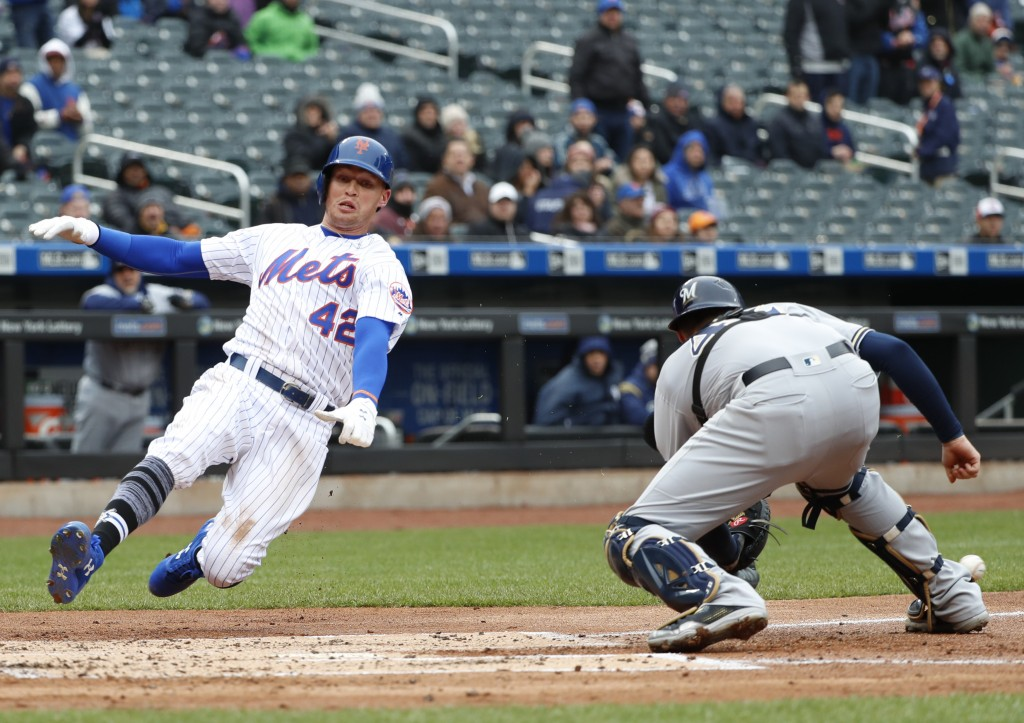 New York Mets Brandon Nimmo comes in feet first to score ahead of the throw to Milwaukee Brewers catcher Jett Bandy in the first inning of a baseball