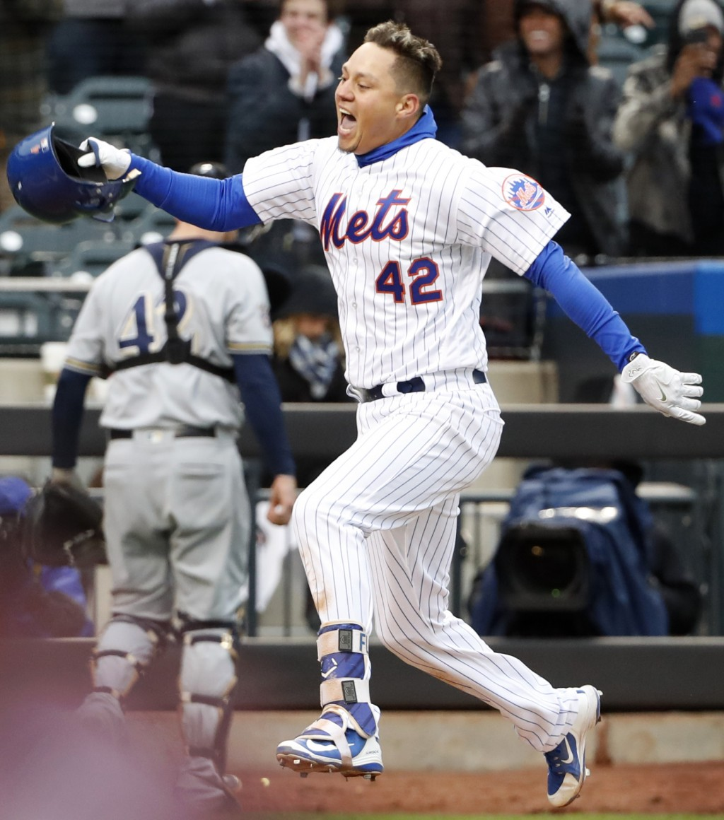 New York Mets' Wilmer Flores celebrates his ninth-inning walkoff home run in a baseball game against the Milwaukee Brewers, Sunday, April 15, 2018, in