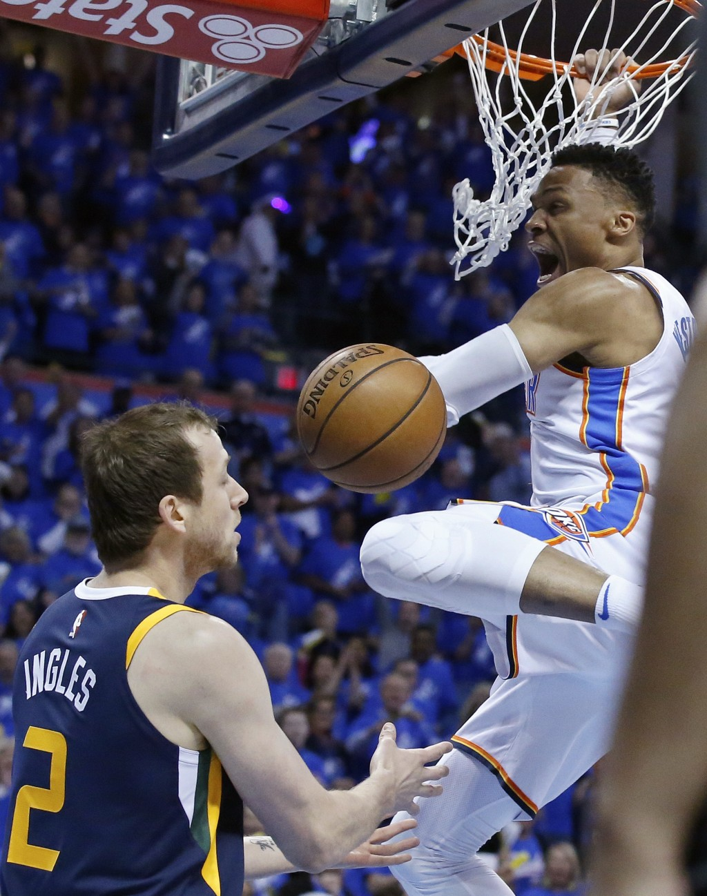 Oklahoma City Thunder guard Russell Westbrook, right, dunks in front of Utah Jazz forward Joe Ingles (2) in the first half of Game 1 of an NBA basketb
