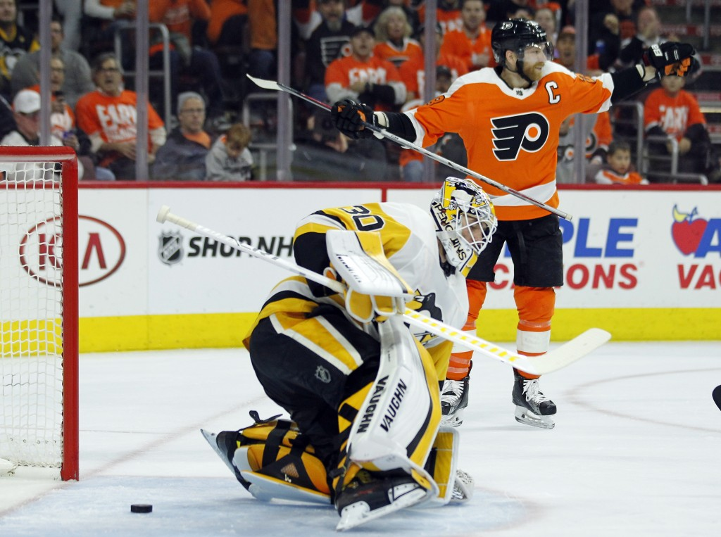 Philadelphia Flyers' Claude Giroux, back right, raises his arms after a shot by Travus Sanheim (not shown) got past Pittsburgh Penguins goalie Matthew
