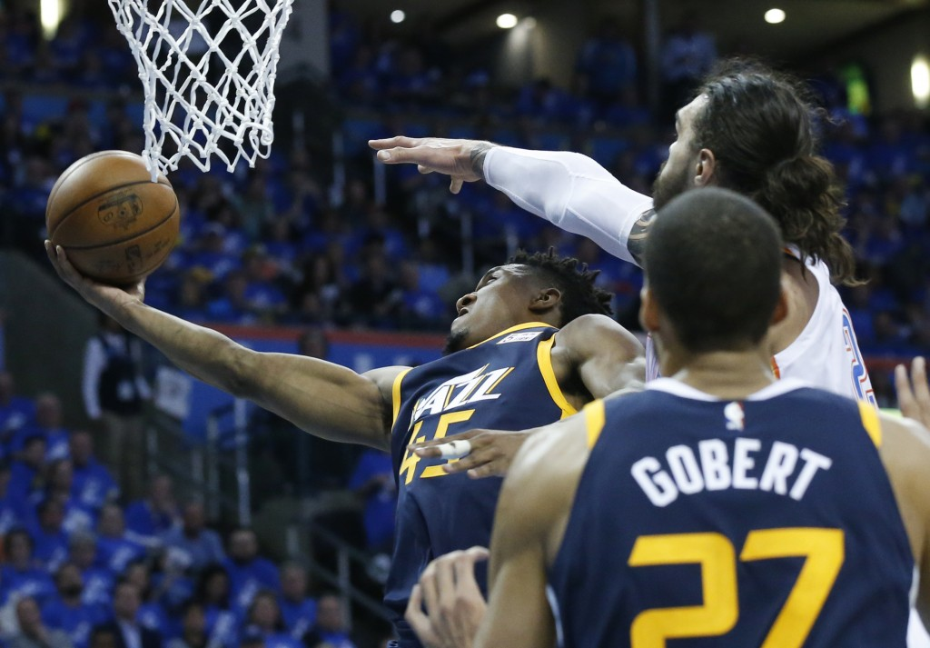 Utah Jazz guard Donovan Mitchell (45) shoots as Oklahoma City Thunder center Steven Adams, right, defends from behind in the second half of Game 1 of