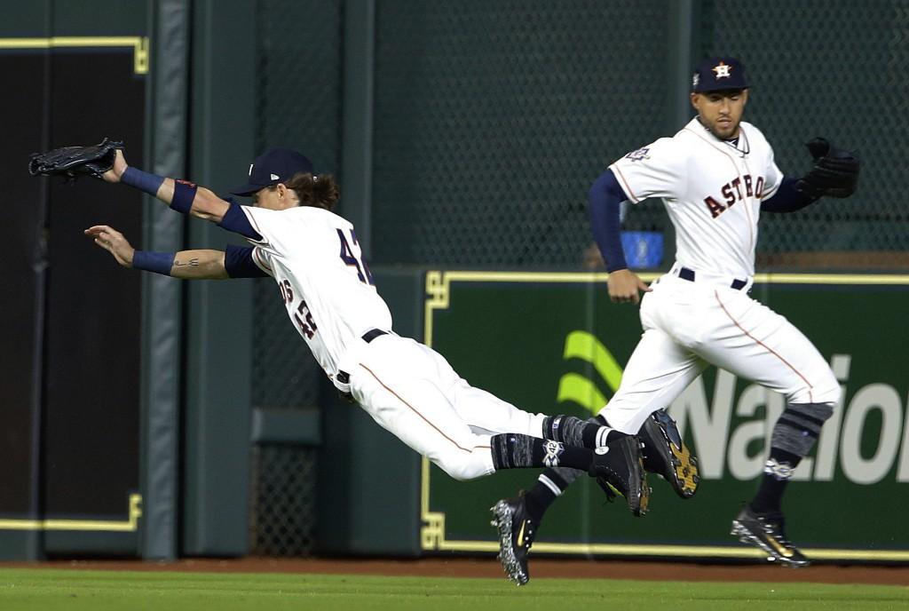 Houston Astros right fielder Josh Reddick, left, makes the catch on a line drive by Texas Rangers' Adrian Beltre as he crosses center fielder George S