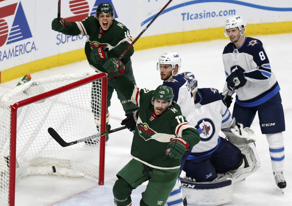 Minnesota Wild left wing Marcus Foligno (17) and Wild center Joel Eriksson Ek (14) celebrate after Foligno scored a goal on Winnipeg Jets goalie Conno