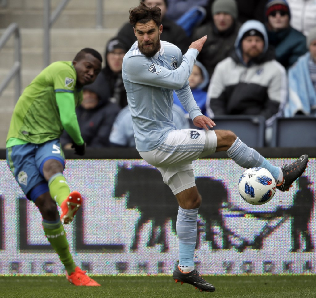 Sporting Kansas City midfielder Graham Zusi, right, blocks a kick by Seattle Sounders defender Nouhou Tolo (5) during the first half of an MLS soccer