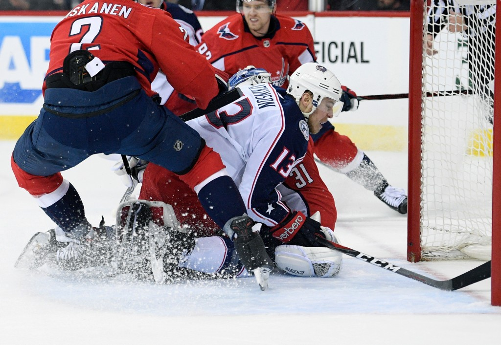 Columbus Blue Jackets right wing Cam Atkinson (13) collides into Washington Capitals goaltender Philipp Grubauer (31), of Germany, during the first pe