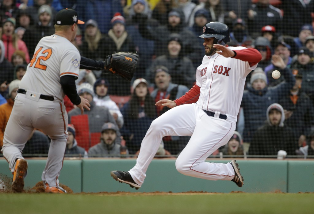 Boston Red Sox's J.D. Martinez, right, scores on a wild pitch by Baltimore Orioles' Dylan Bundy, left, in the sixth inning of a baseball game Sunday,