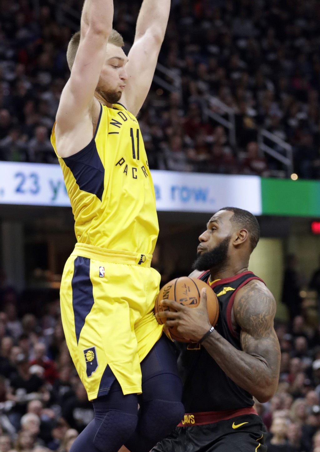 Cleveland Cavaliers' LeBron James, right, is stopped by Indiana Pacers' Domantas Sabonis, from Lithuania, in the first half of a first-round playoff s