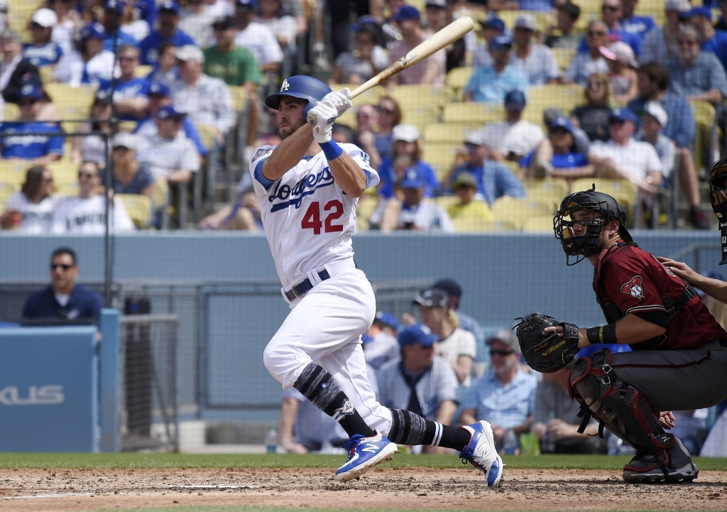Los Angeles Dodgers' Chris Taylor, left, hits a solo home run during the fourth inning of a baseball game as Arizona Diamondbacks catcher Jeff Mathis