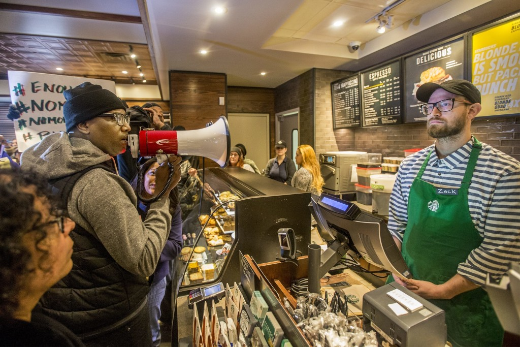 Local Black Lives Matter activist Asa Khalif, left, stands inside a Starbucks, Sunday April 15, 2018, demanding the firing of the manager who called p