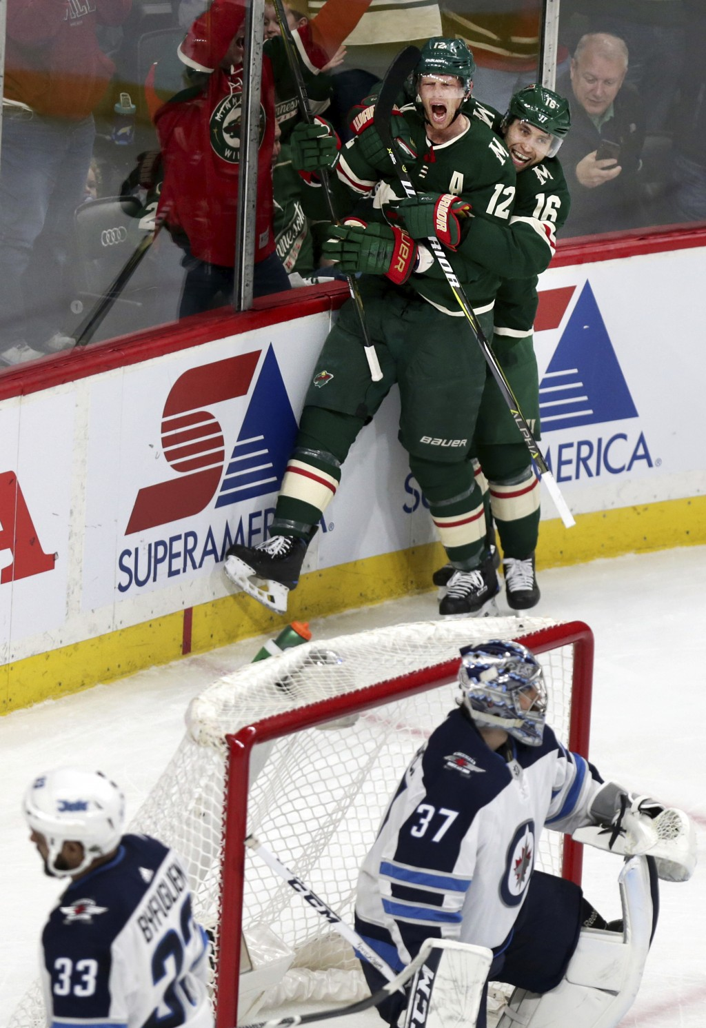 Minnesota Wild center Eric Staal (12) and Wild left wing Jason Zucker (16) celebrate after Staal scored a goal on Winnipeg Jets goalie Connor Hellebuy