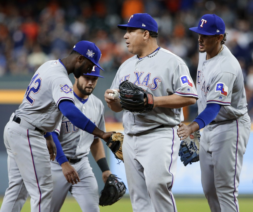 Texas Rangers, center, starting pitcher Bartolo Colon is congratulated by team mates Adrian Beltre, Isiah Kiner-Falefa and Ronald Guzman as he leaves