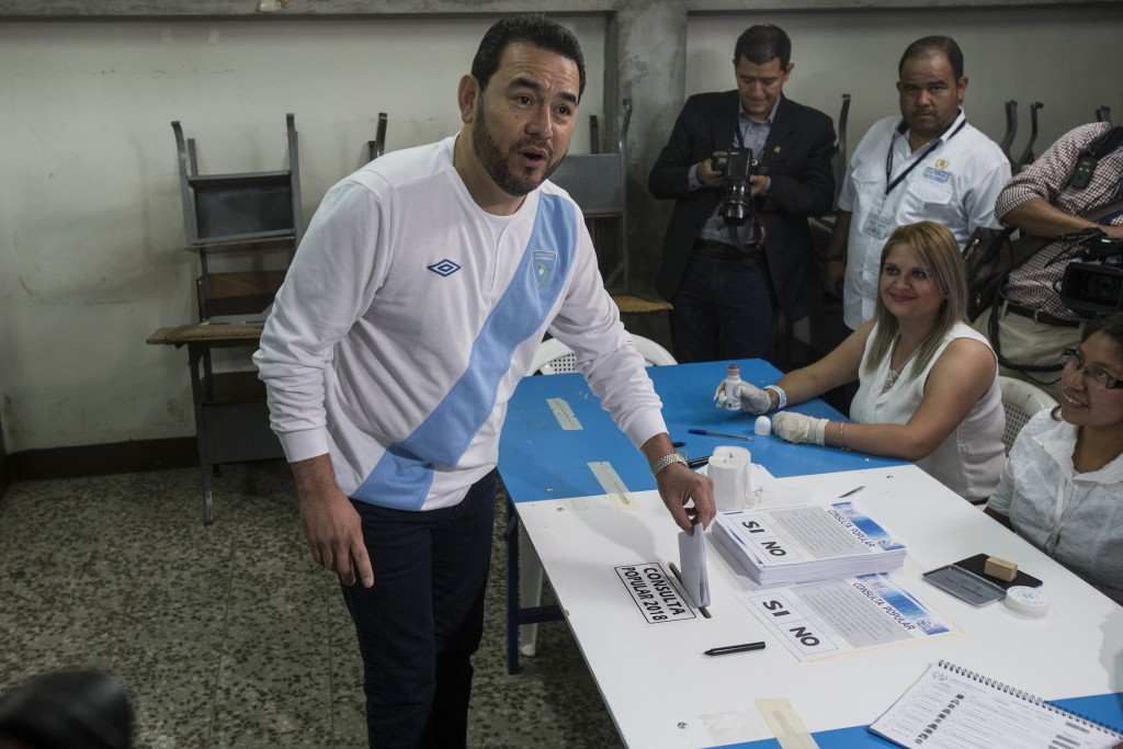 Guatemalan President Jimmy Morales looks to photographers as he casts his vote during a plebiscite on a border dispute with Belize, in Guatemala City,