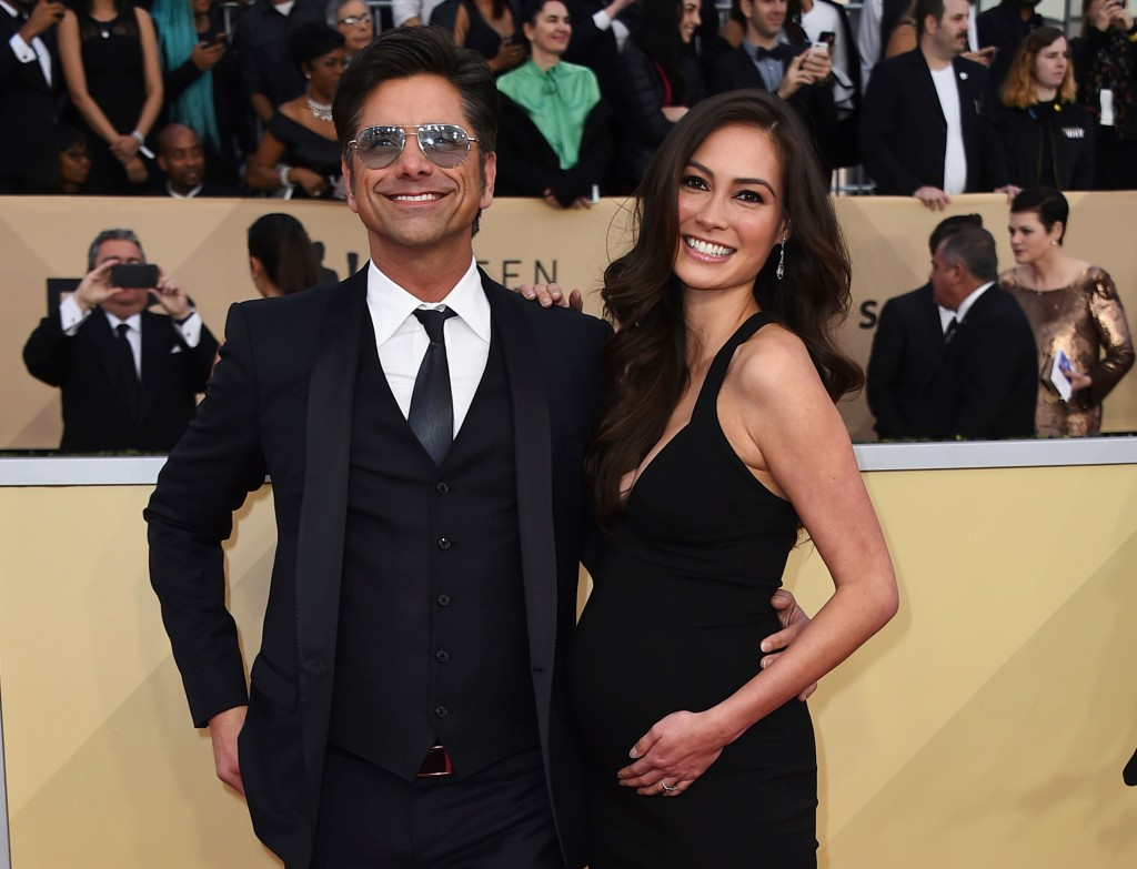 FILE - In this Jan. 21, 2018, file photo, John Stamos, left, and Caitlin McHugh arrive at the 24th annual Screen Actors Guild Awards at the Shrine Aud