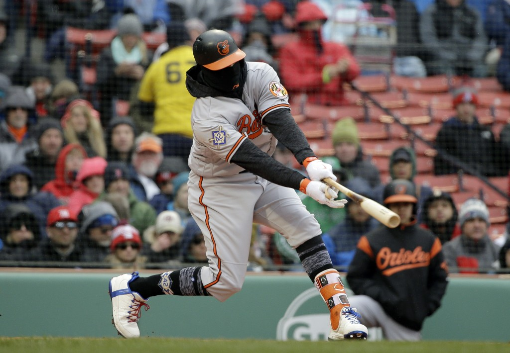 Baltimore Orioles' Manny Machado hits an RBI-double off a pitch by Boston Red Sox's Chris Sale in the first inning of a baseball game Sunday, April 15