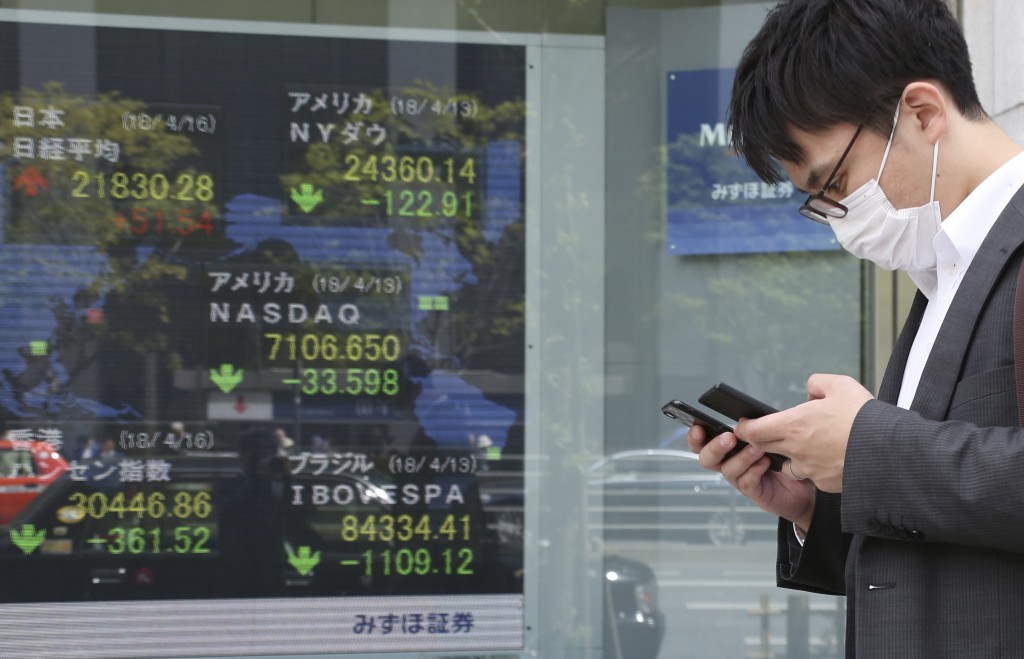 A man walks by an electronic stock board of a securities firm in Tokyo, Monday, April 16, 2018. Shares were mixed in Asia after an upbeat start to the