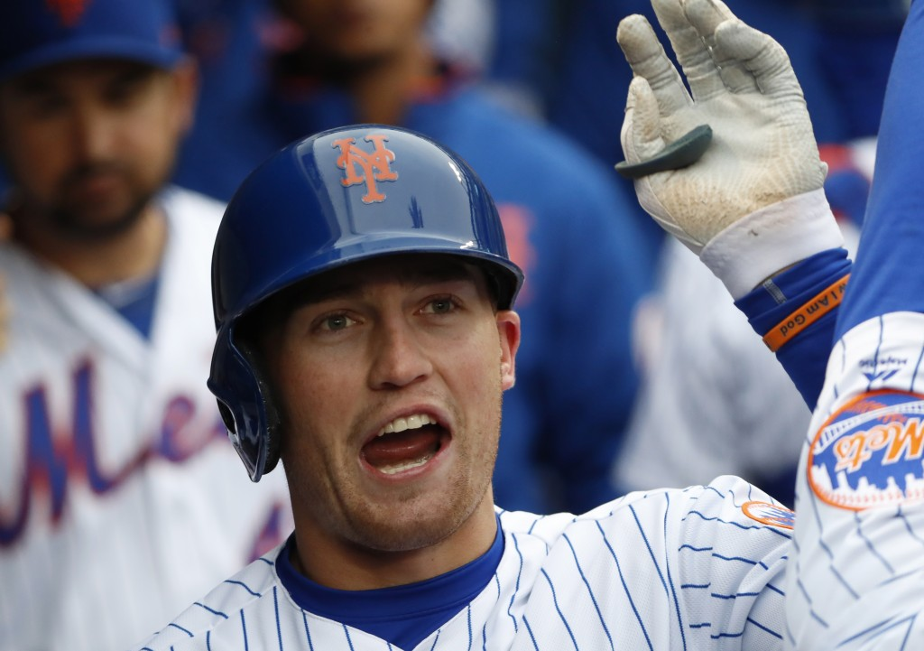 New York Mets' Brandon Nimmo celebrates with teammates in the dugout after hitting a solo home run in the sixth inning of a baseball game against the