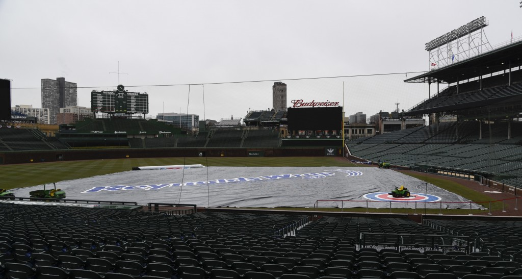 The tarp lays on Wrigley Field after a baseball game between the Atlanta Braves and the Chicago Cubs was postponed on Sunday, April 15, 2018, in Chica