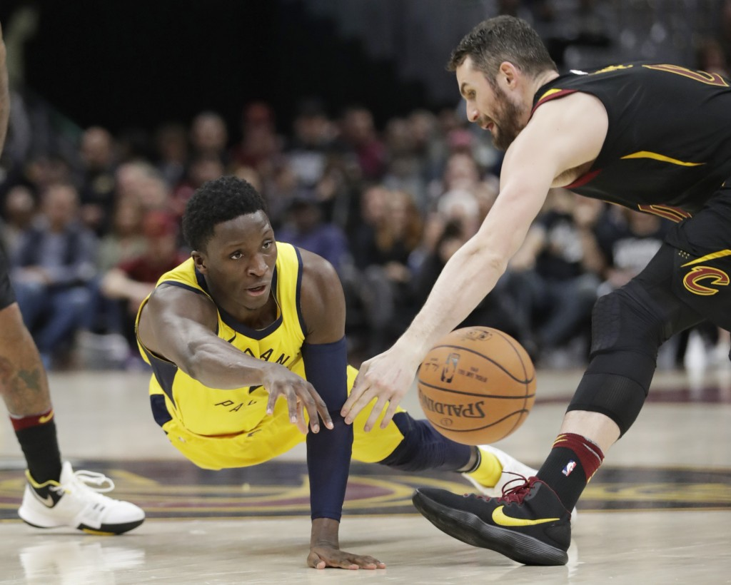 Indiana Pacers' Victor Oladipo, left, passes against Cleveland Cavaliers' Kevin Love in the second half of Game 1 of an NBA basketball first-round pla