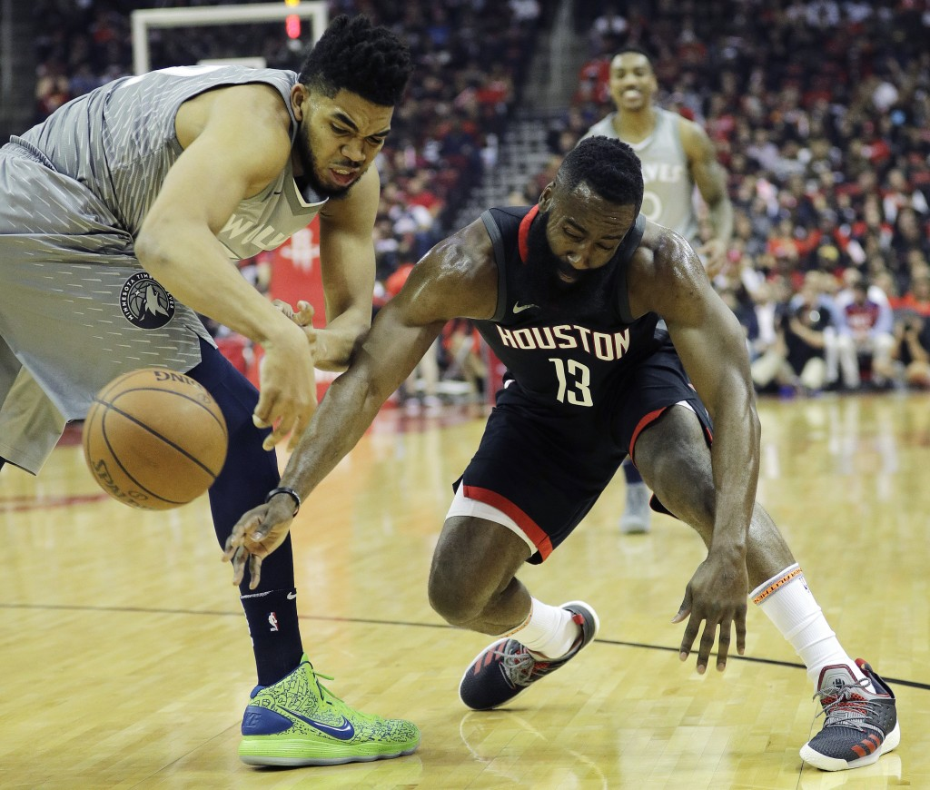 Houston Rockets' James Harden, right, vies for the ball with Minnesota Timberwolves' Karl-Anthony Towns during the first half in Game 1 of a first-rou