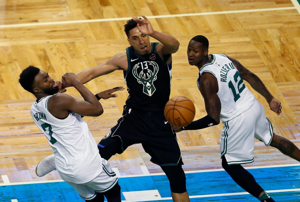 Milwaukee Bucks' Malcolm Brogdon (13) passes off under pressure from Boston Celtics' Jaylen Brown (7) and Terry Rozier (12) during the second quarter