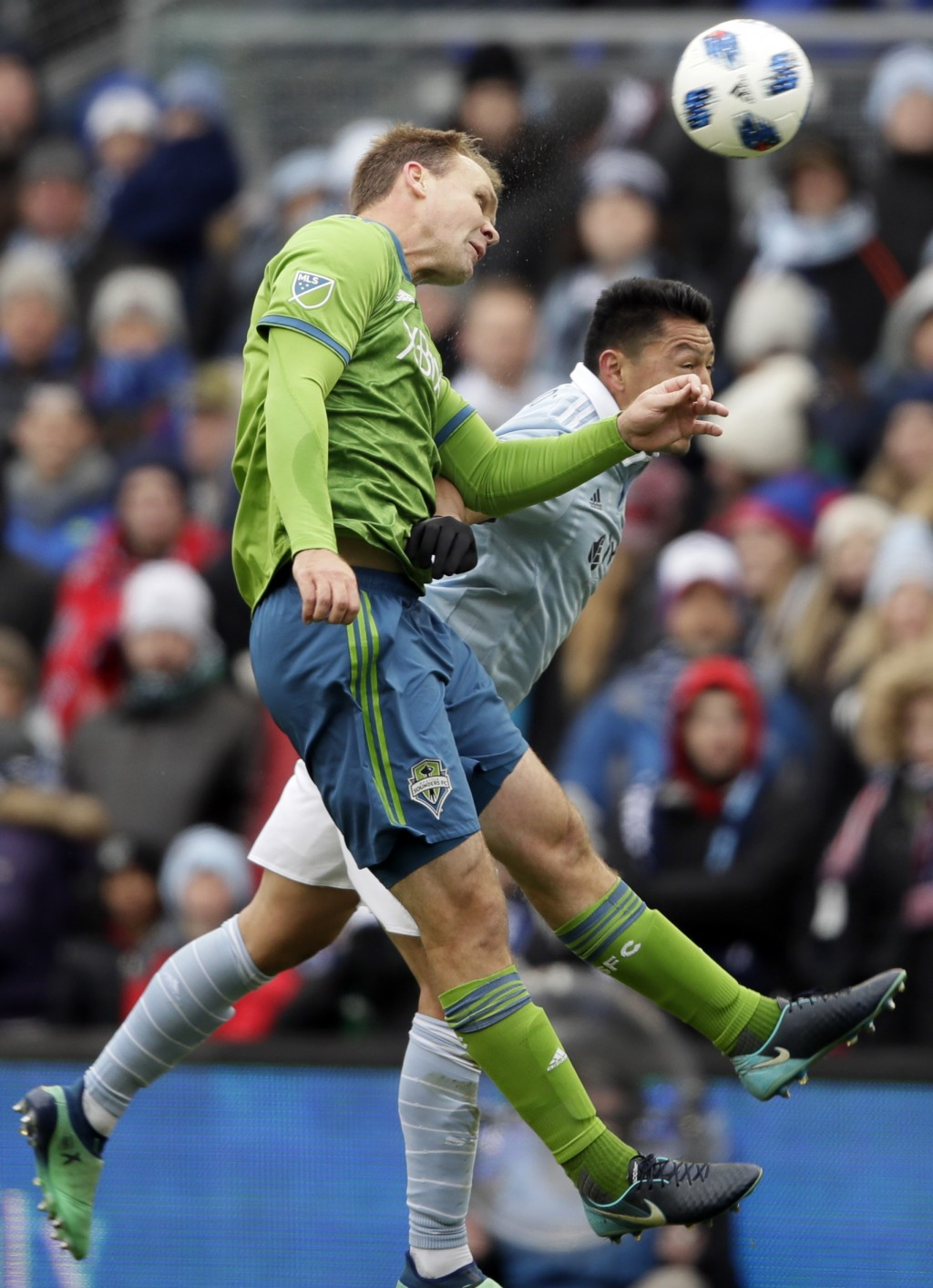 Seattle Sounders defender Chad Marshall, front, heads the ball against Sporting Kansas City midfielder Roger Espinoza, back, during the first half of